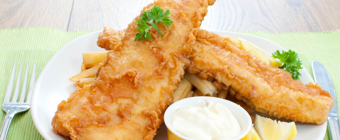 Two golden fried fish fillets on a plate with tartar sauce and lemon slices