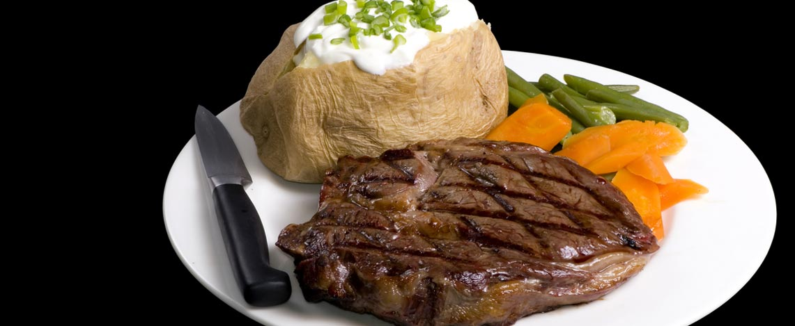 Grilled sirloin steak with a loaded baked potato and vegetables